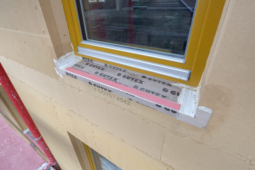 Dichte Gebäudehülle mit wind- und schlagregensicheren Fensteranschlüssen aus der Vorfertigung: Dank des geprüften Fensteranschluss-Systems Implio F von GUTEX stehen auf der Baustelle nur noch Putzarbeiten an.