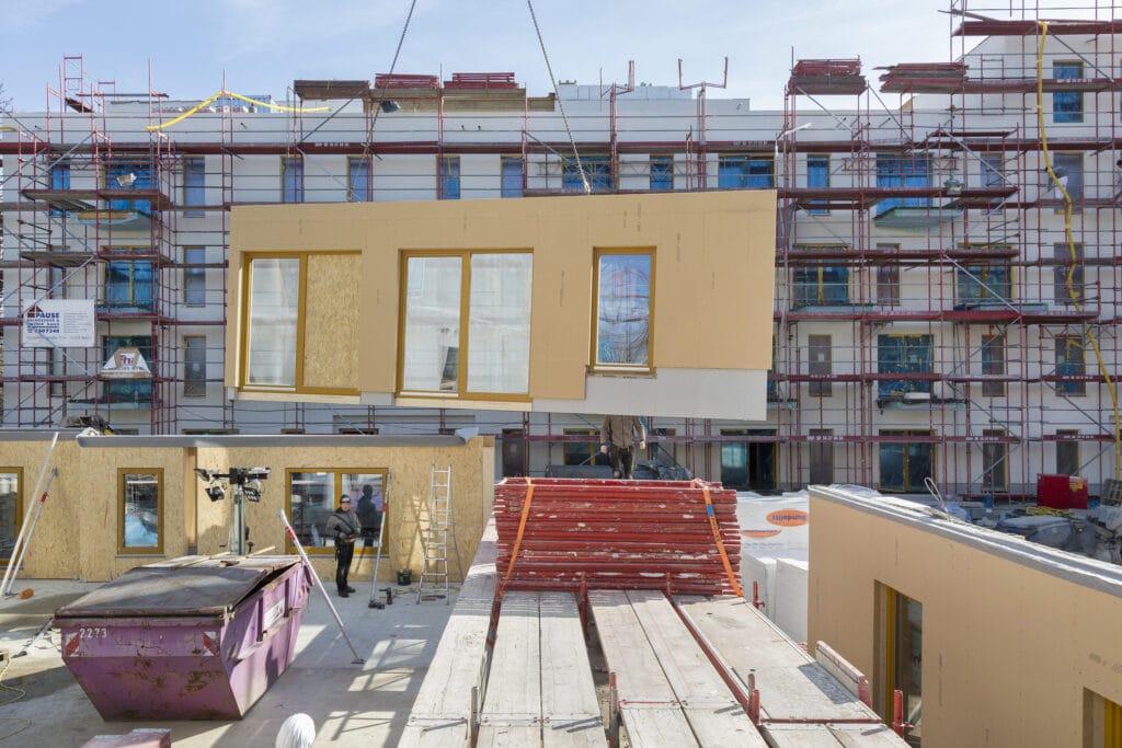 Kurze Bauzeit und geringe Baukosten dank hohem Vorfertigungsgrad: Fassadenelemente mit werkseitig integrierten Fenstern werden montagefertig auf die Baustelle geliefert. (Bildquelle: Jens Schumann)